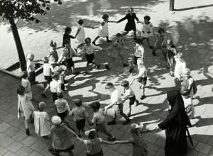 Kinderen lopen [tijdens het speelkwartier] in een kring op het schoolplein van een kleuterschool. [1938]. Plaats onbekend.