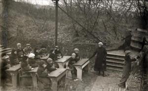 Openluchtscholen: Een klas leerlingen krijgt les met schoolborden en al buiten in de open lucht. Ze zijn dik bepakt om de kou te trotseren. Plaats onbekend, 1918.